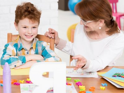 Happy little boy with mental disorder having private reading lesson with children therapist